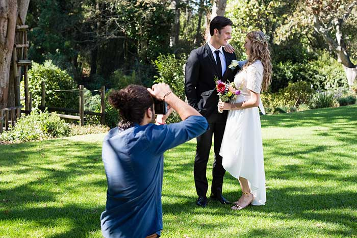 wedding photographer taking photo of-newly-married-couple